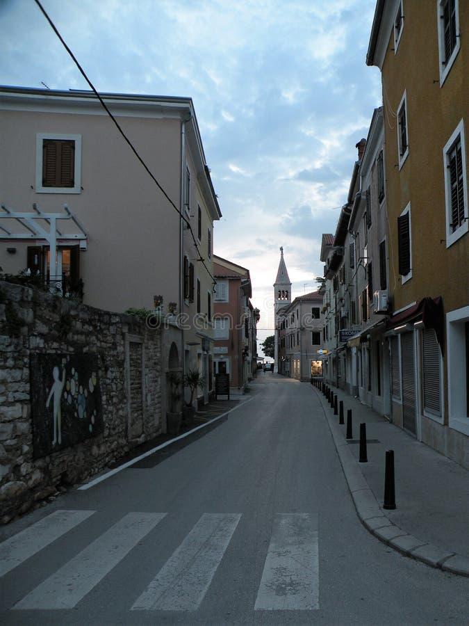 Oude Istrian-stad van Novigrad, Kroatië Een mooie kerk met een hoge elegante klokketoren, steenstegen en een oud Mediterraan huis stock afbeeldingen