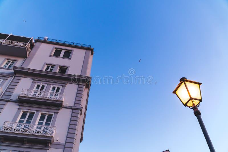 Oude Italiaanse flatgebouwen op een zonsondergang met een blauwe hemel en een straatlantaarn Voorgevel van flatgebouw, hotels, he stock fotografie