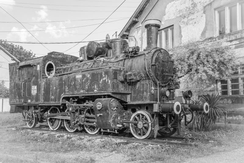 Oude Joegoslaafse locomotief dichtbij oud zwart-wit station, royalty-vrije stock fotografie