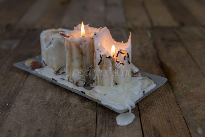 Oude kaarsen met vuile was op een houten lijst Brandende vuile cand stock afbeelding