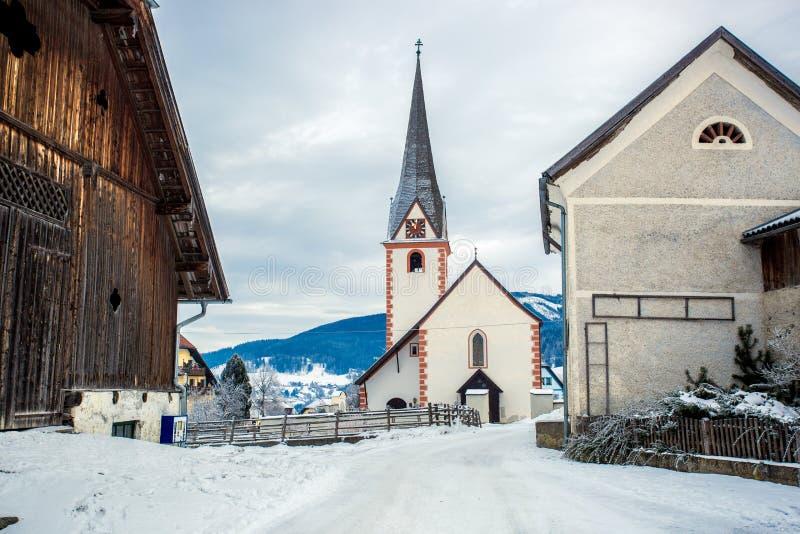 Oude katholieke kerk in kleine Oostenrijkse die stad door sneeuw wordt behandeld stock foto