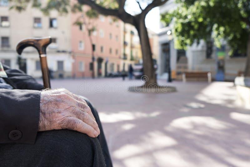 Oude Kaukasische mens, die in een bank in openlucht zitten stock foto