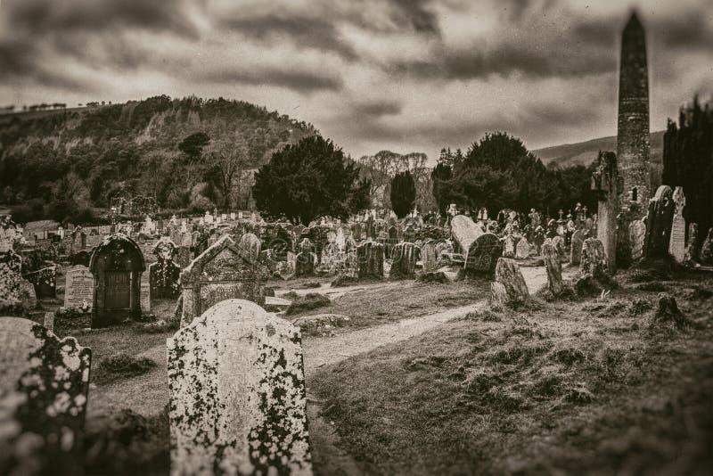 Oude oude Keltische begraafplaats en grafstenen hoge toren op berg en stormachtige hemelachtergrond in sepia stijl stock foto's