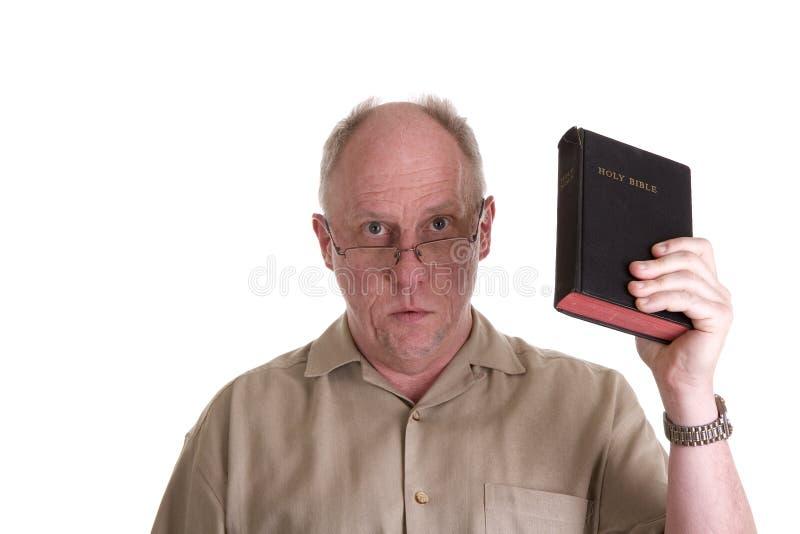 Oude Kerel in de Bruine Bijbel van het Overhemd en van de Holding van Glazen stock foto