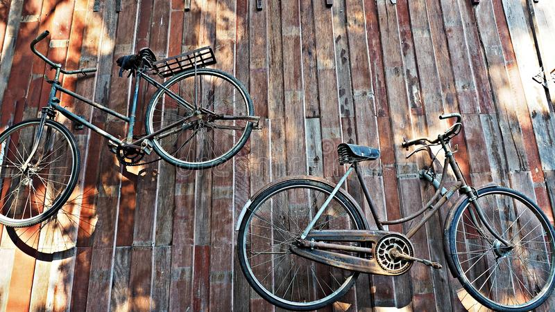 Oude klassieke fietsen die op houten muur hangen royalty-vrije stock foto's