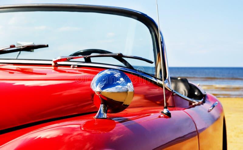 Oude klassieke rode jaguar bij strand stock afbeelding
