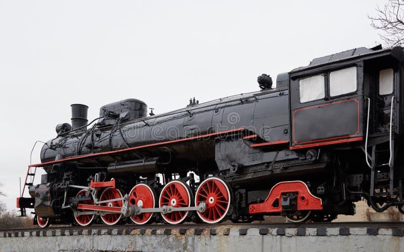 Oude klassieke zwarte stoomlocomotief met rode decoratie op spoorwegspoor royalty-vrije stock afbeeldingen