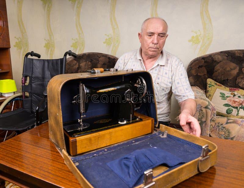 Oude Kleermaker Man Closing een Geval met Naaimachine stock afbeeldingen