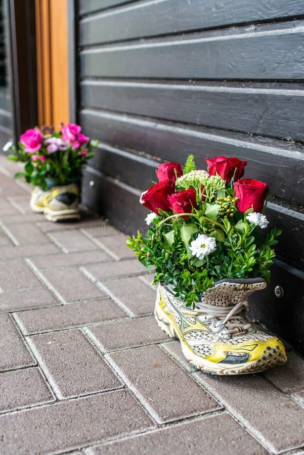 Oude kleurrijke die sportenschoenen als vaas van de bloempot voor een huwelijksdecoratie worden gebruikt royalty-vrije stock fotografie