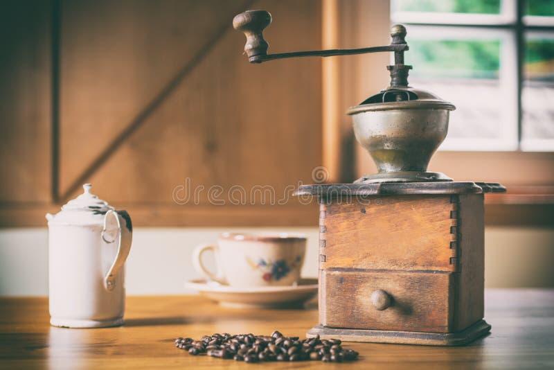 Oude koffiemolen in een rustieke boerderij met koffiebonen, melkkruik en koffiekop stock afbeelding