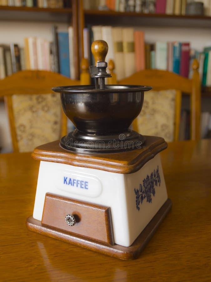 Oude koffieslijper op tafel stock afbeelding
