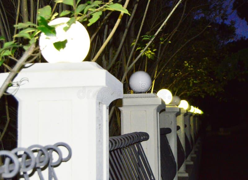 Oude kolommen met lichten langs de gang in het Park bij nacht stock fotografie