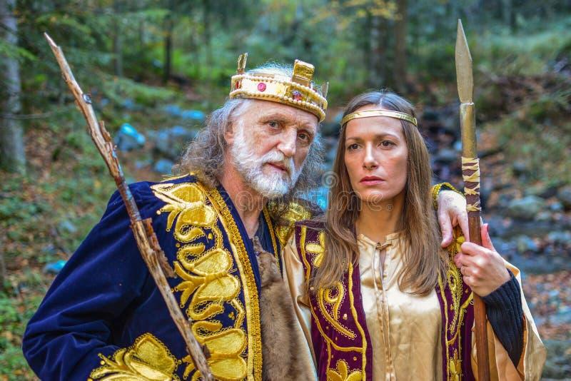 Oude koning en koningin in het bos stock afbeelding