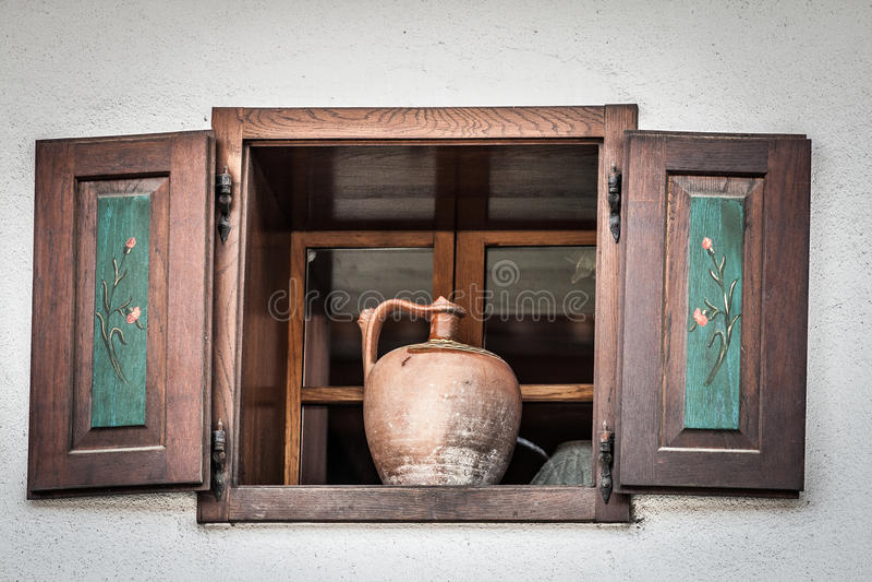 Oude kruik die zich in wijd open houten venster bevinden stock afbeelding
