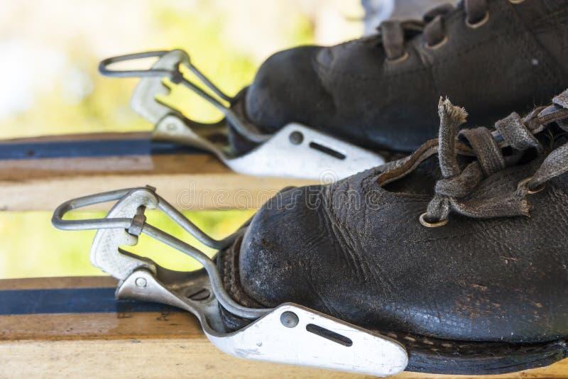 Oude laarzen in skiklemmen stock afbeelding