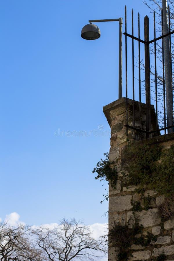 Oude lamp op de omheining Hoge lamp op linker en mooie blauwe hemelachtergrond voor exemplaarruimte stock foto's