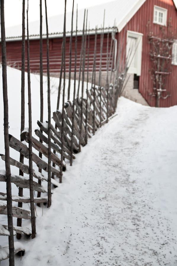 Oude landbouw rode traditionele schuur op idyllische landelijke landbouwgrond, boerderijweg met sneeuw en rustieke oude houten om stock foto