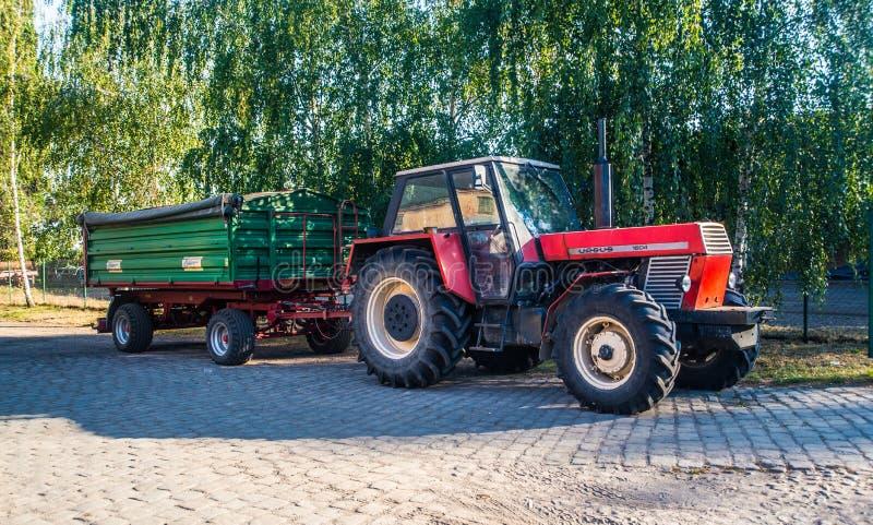 Oude landbouwbedrijftractor met aanhangwagen stock afbeelding