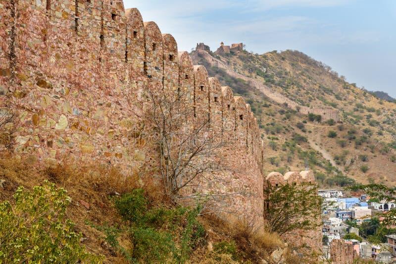 Oude lange muur met torens rond Amber Fort en mening van Amberdorp Rajasthan India stock afbeelding