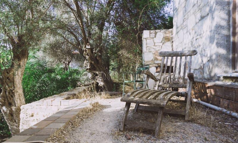 Oude lange stoel in de tuin stock foto's