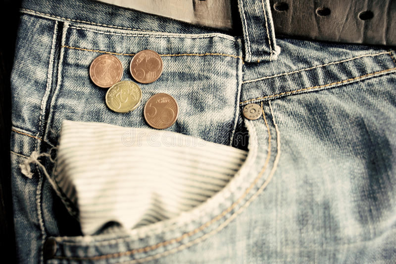 Oude langzaam verdwenen jeans met euro muntstukken in lege zak royalty-vrije stock fotografie