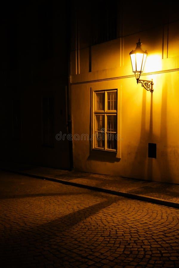 Oude lantaarn die een donkere steeg middeleeuwse straat verlichten bij nacht in Praag, Tsjechische Republiek Rustige foto stock fotografie