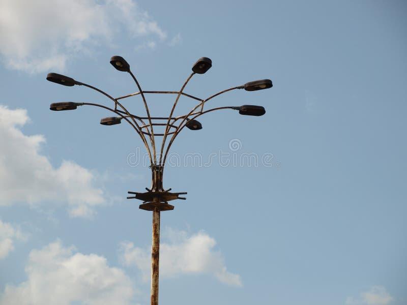 Oude lantaarnpaal met acht lantaarns op een achtergrond van blauwe hemel stock foto's