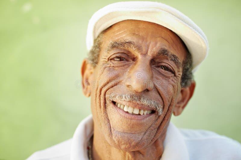 Oude latino mens die bij camera glimlacht stock foto's