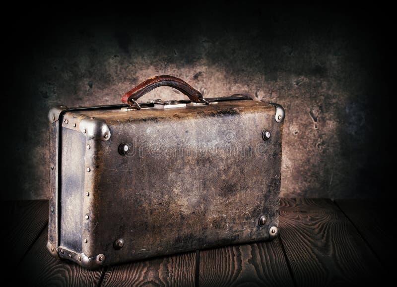 Oude leerkoffer op een houten lijst stock afbeeldingen