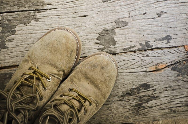 Oude leerschoenen op houten vloer royalty-vrije stock afbeelding