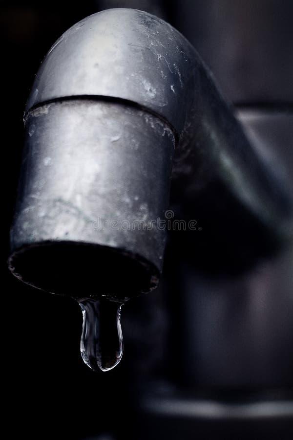 Oude lekke tapkraannadruk op waterdaling stock foto's