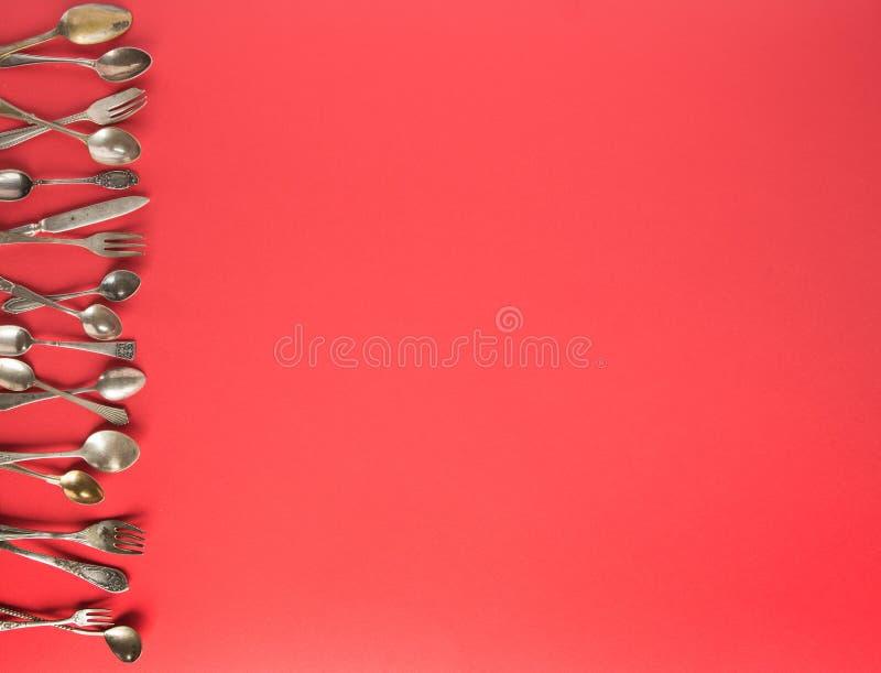 Oude lepels en vorken op een rode achtergrond Plaats voor tekst stock foto's