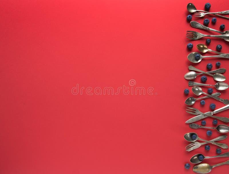 Oude lepels, vorken en messen, en bosbessen op een rode achtergrond Plaats voor tekst royalty-vrije stock fotografie