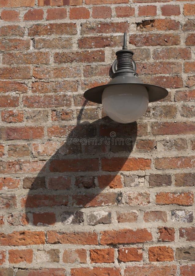 Oude lichte montage op rode bakstenen muur gietende schaduw royalty-vrije stock foto's