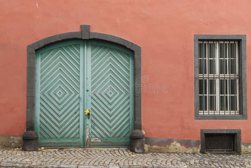 Oude lichtgroene houten deur in oker concrete muur met venster stock afbeelding