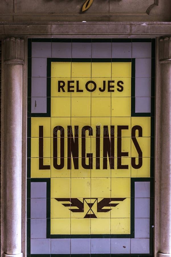 Oude Longines let reclame op affiche die van tegels wordt gemaakt stock foto's