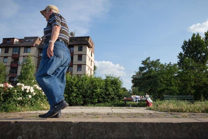Oude man die dichtbij een hogere vrouwenslaap lopen op een bank, in het district van Doni Dorcol, Belgrado royalty-vrije stock foto's