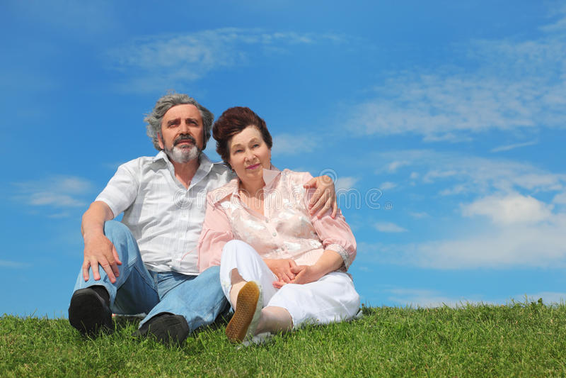 Oude man en vrouwenzitting op groen gazon stock foto