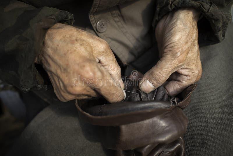Handen die aan een laars werken stock foto