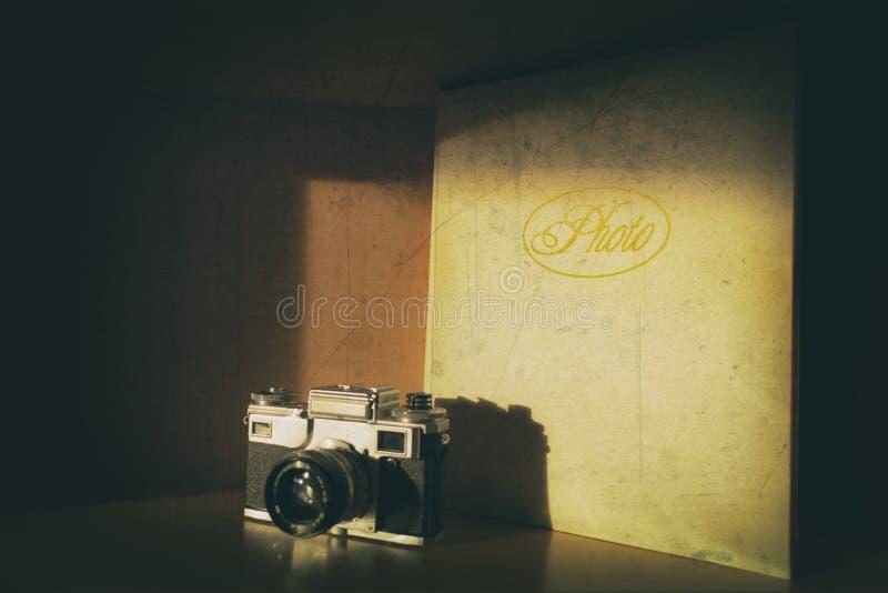 Oude manier retro analoge camera die naast het grote album van de leerfoto zich lichtjes in de schaduw bevinden Oude beschadigde  stock foto