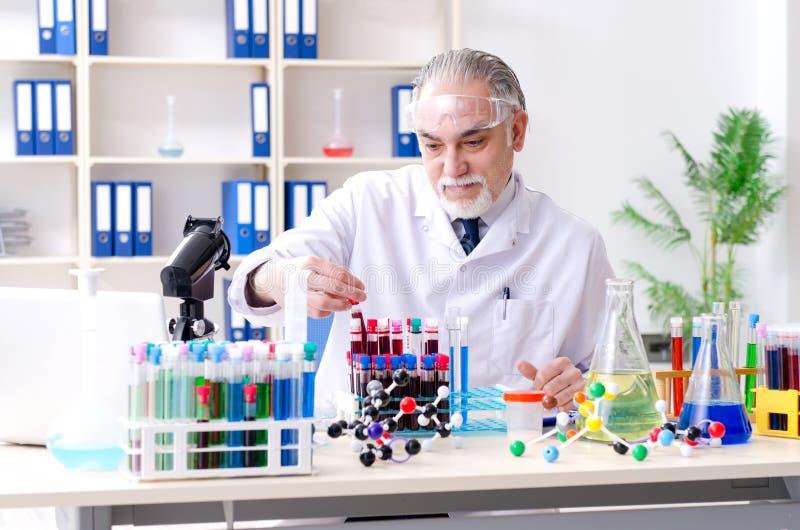Oude mannelijke chemicus die in het laboratorium werken royalty-vrije stock foto