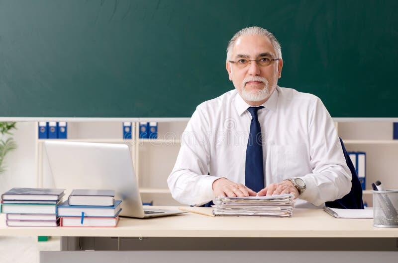 Oude mannelijke leraar voor bord stock afbeelding