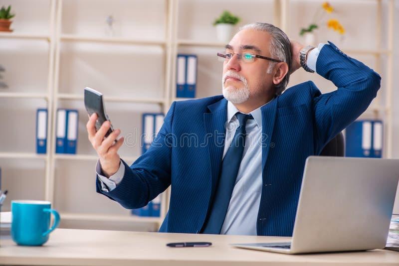 Oude mannelijke werknemer die in het bureau werken stock afbeelding