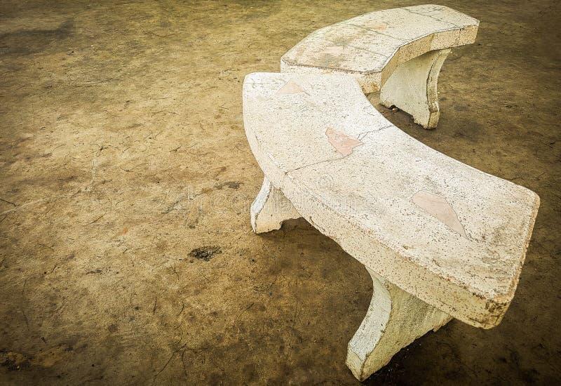 Oude marmer gebogen stoel op concrete vloer stock afbeeldingen