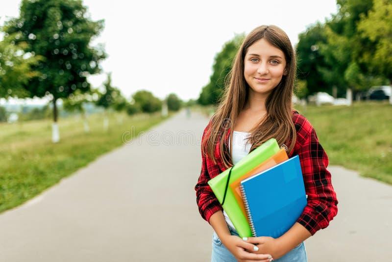 Oude meisjesschoolmeisje 13-16 het jaar is in de zomer in stad in de omslagen van een notitieboekjehandboeken Vrije ruimte voor t stock afbeeldingen