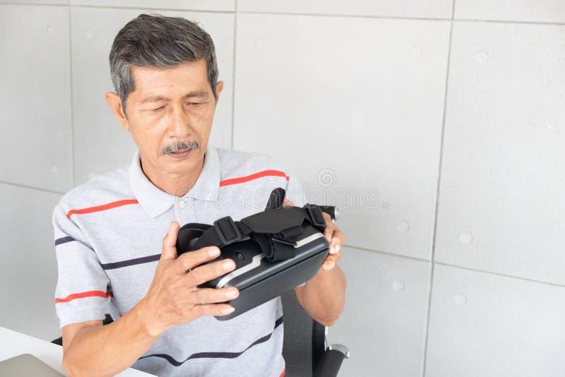 Oude mens in de glazen van de vrwerkelijkheid van virtuele werkelijkheid met het spelen van spel stock afbeelding