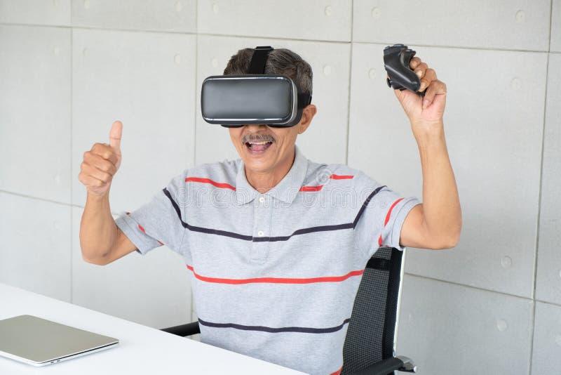 Oude mens in de glazen van de vrwerkelijkheid van virtuele werkelijkheid met het spelen van spel royalty-vrije stock foto's