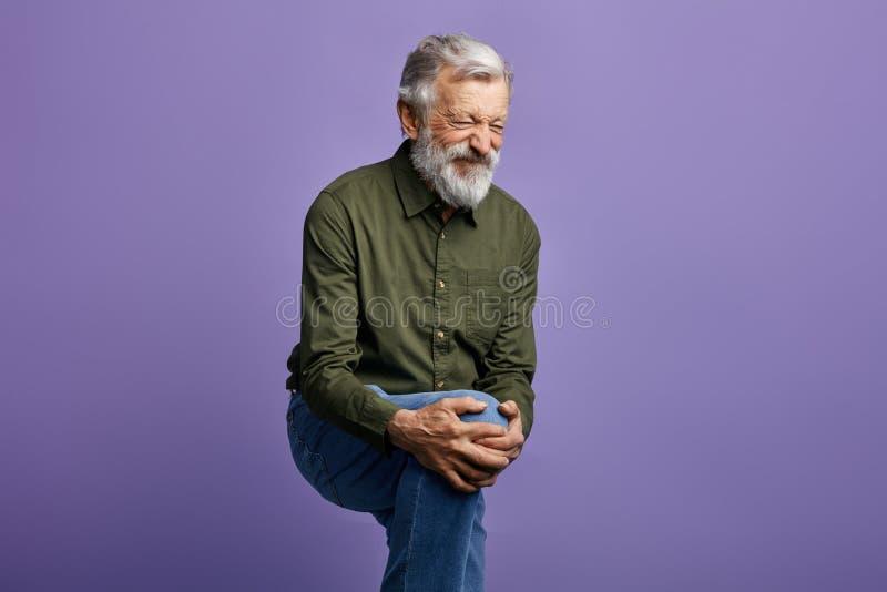 Oude mens die aan kniepijn lijden die op blauwe achtergrond wordt geïsoleerd stock afbeelding