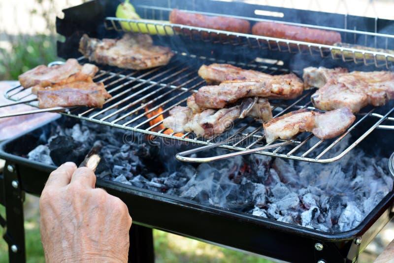 Oude mens die barbecue voorbereiden royalty-vrije stock afbeeldingen