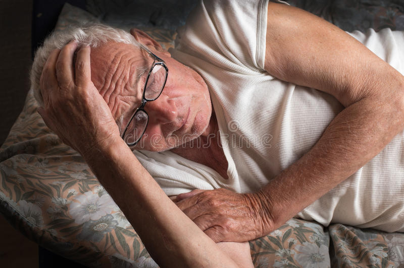 Oude mens die in bed liggen stock foto's